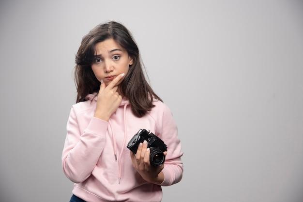 Vrouwelijke fotograaf met camera die zich op grijze muur bevindt.