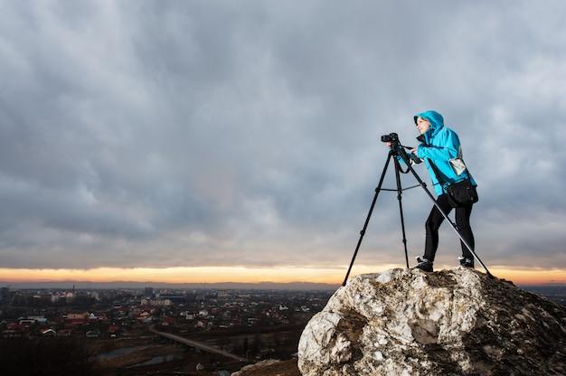 Vrouwelijke fotograaf met camera op statief op de grote rots