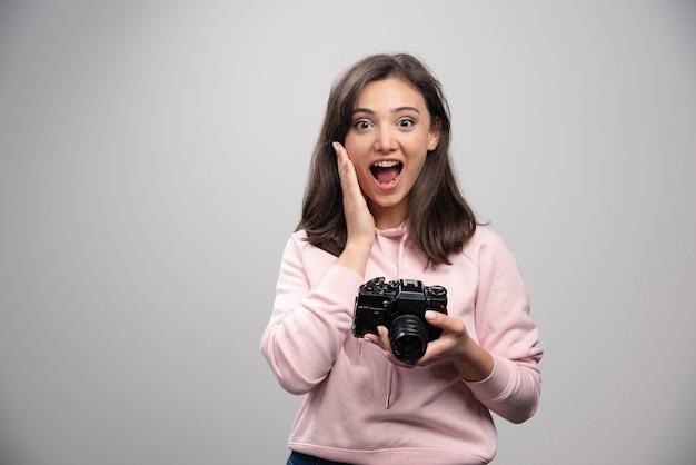 Vrouwelijke fotograaf poseren met camera op grijze muur.