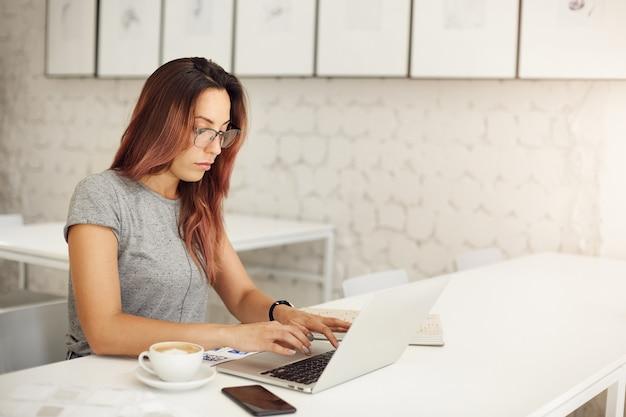 Vrouwelijke freelance scenarioschrijver die laptop gebruikt om haar nieuwe meesterwerk in een café weg van huis te creëren om haar creatieve blok te bestrijden.