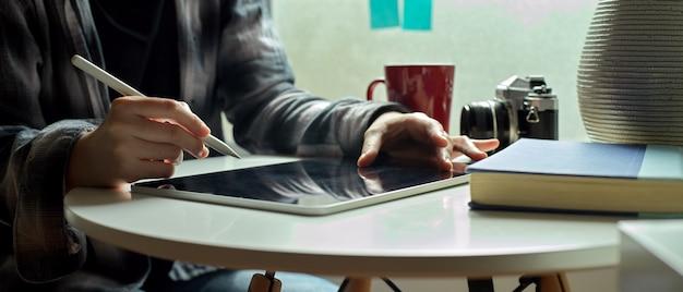Vrouwelijke freelancer die aan digitale tablet met naaldpen werkt aan koffietafel naast venster