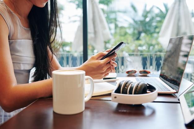 Vrouwelijke freelancer die berichten op sociale media beantwoordt tijdens het werken aan tafel in coffeeshop