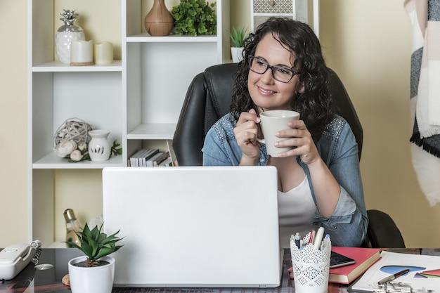 Vrouwelijke freelancer die met mok hete drank rust