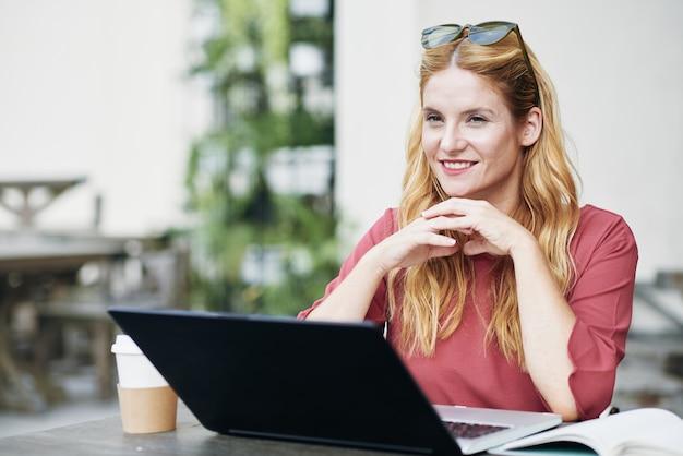 Vrouwelijke freelancer die op laptop werkt