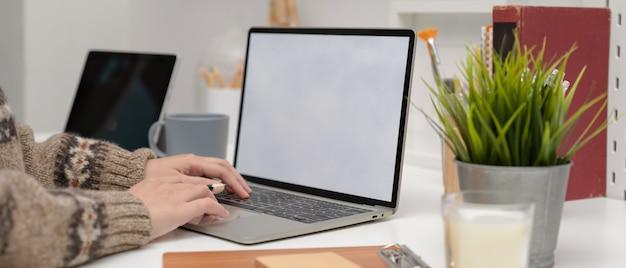 Vrouwelijke freelancer typen op mock-up laptop op minimale werkruimte met benodigdheden en decoraties