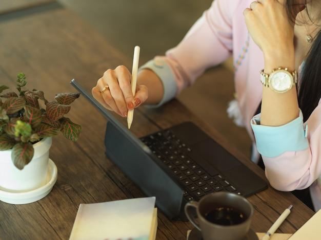 Vrouwelijke freelancer werken met digitale tablet op houten tafel in café
