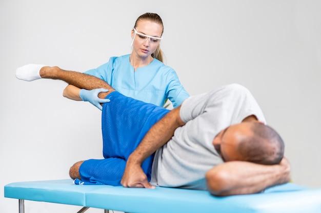 Vrouwelijke fysiotherapeut die de beenflexibiliteit van de man controleert Premium Foto