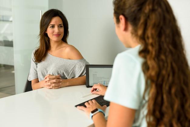 Vrouwelijke fysiotherapeut die diagnose verklaart aan haar vrouwenpatiënt.