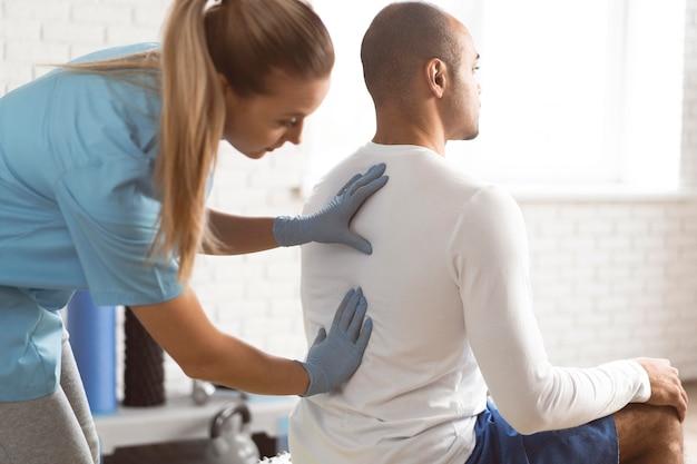 Vrouwelijke fysiotherapeut die man terug controleert