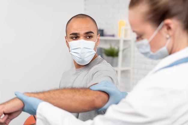 Vrouwelijke fysiotherapeut met medisch masker en handschoenen die man elleboog controleren