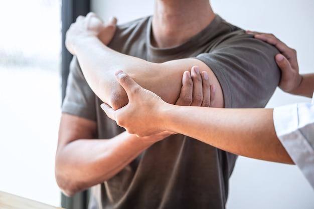 Vrouwelijke fysiotherapeut werken behandeling van gewonde arm van atleet mannelijke patiënt onderzoeken