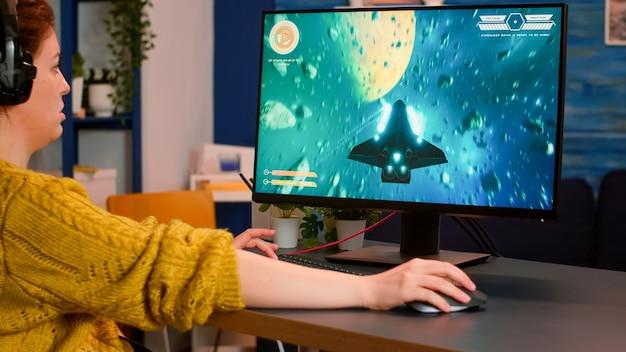 Vrouwelijke gamer die esports vanuit huis speelt met behulp van een krachtige computer die deelneemt aan het kampioenschap