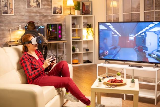 Vrouwelijke gamer die 's avonds laat in de woonkamer videogames speelt met een vr-headset