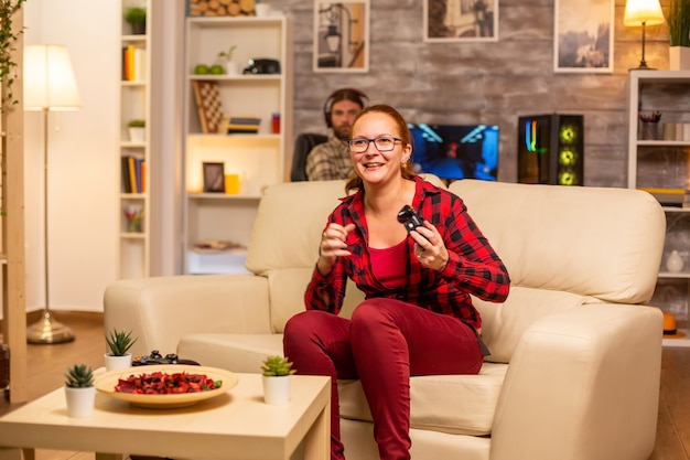 Vrouwelijke gamer die 's avonds laat videogames speelt op de console in de woonkamer