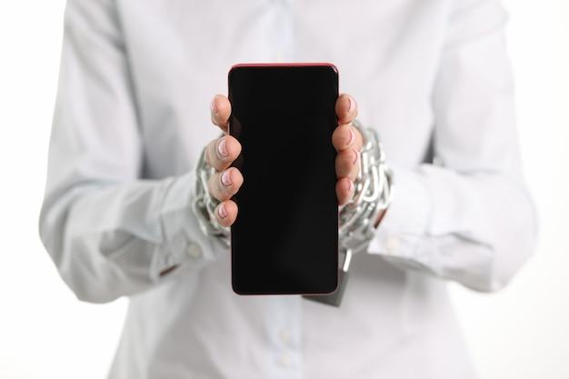 Vrouwelijke gebonden handen met ketting houden smartphone-verslaving en sociale media-concept vast