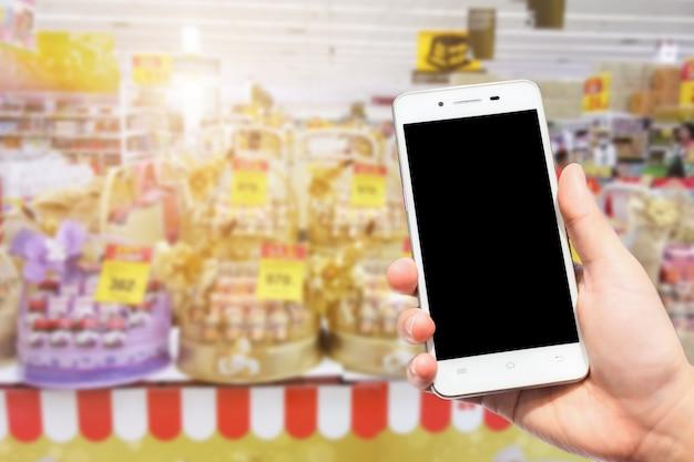 Vrouwelijke gebruik houden smartphone wazig beelden van veel eetbare vogelnest worden gezonde drankjes geschenkmanden te koop bij de supermarkt