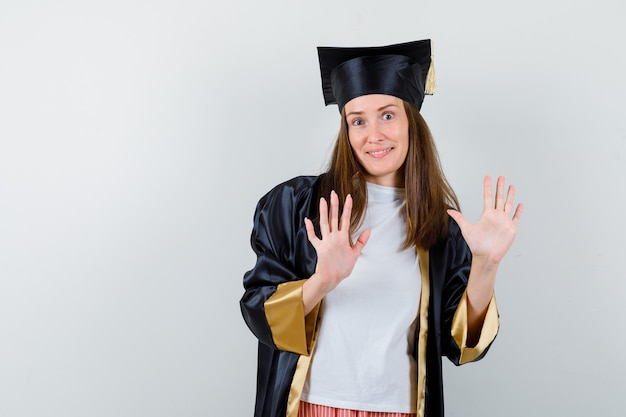 Vrouwelijke gediplomeerde die stopgebaar in uniforme, vrijetijdskleding toont en op zoek zelfverzekerd, vooraanzicht.