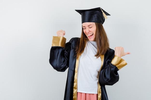 Vrouwelijke gediplomeerde die winnaargebaar in uniforme, vrijetijdskleding toont en zalig kijkt. vooraanzicht.