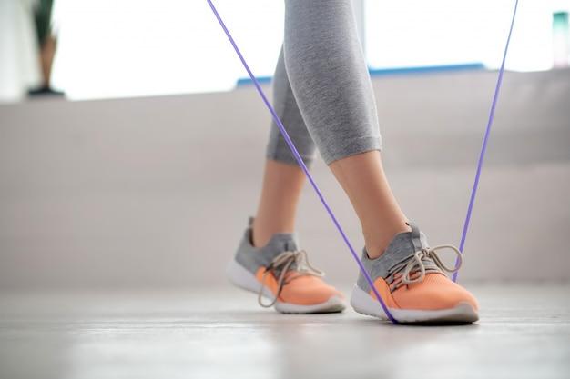 Vrouwelijke geduldige benen die met springtouw lopen
