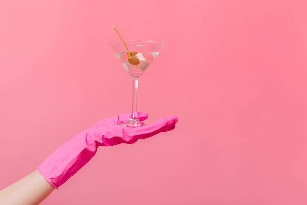Vrouwelijke gehandschoende hand met glas martini met olijf