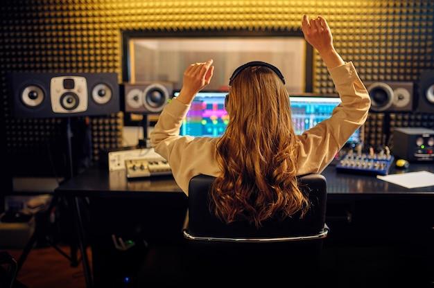 Vrouwelijke geluidstechnicus bij het mengen van consol, achteraanzicht, opnamestudio interieur op achtergrond. synthesizer en audiomixer, muzikantenwerkplek, creatief proces