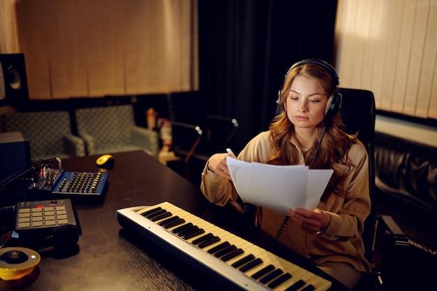 Vrouwelijke geluidstechnicus in koptelefoon, opnamestudio interieur op achtergrond. synthesizer en audiomixer, muzikantenwerkplek, creatief proces
