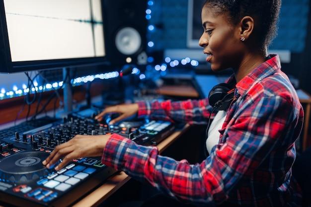 Vrouwelijke geluidstechnicus werkzaam bij het afstandsbedieningspaneel in de opnamestudio. muzikant bij de mixer, professionele audiomixing