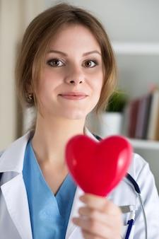 Vrouwelijke geneeskunde arts houden in handen rode stuk speelgoed hart close-up. cardiotherapeut, arts maakt hartfysiek, hartslagmeting of aritmieconcept