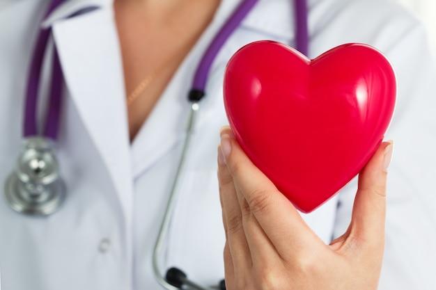 Vrouwelijke geneeskunde arts houdt in handen rode speelgoed hart close-up. cardiotherapeut, arts maakt hartfysiek, hartslagmeting of aritmieconcept