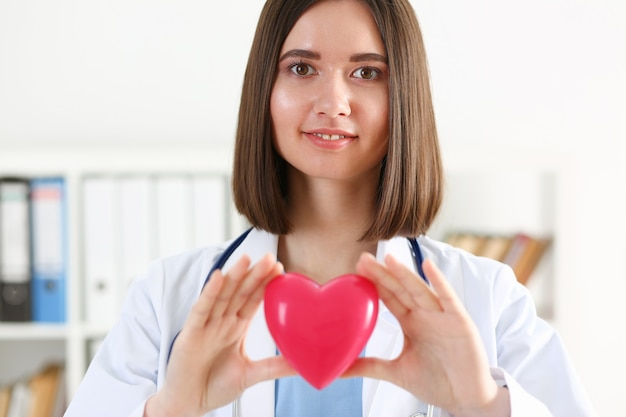 Vrouwelijke geneeskunde arts houdt in handen rood stuk speelgoed hart voor haar borst
