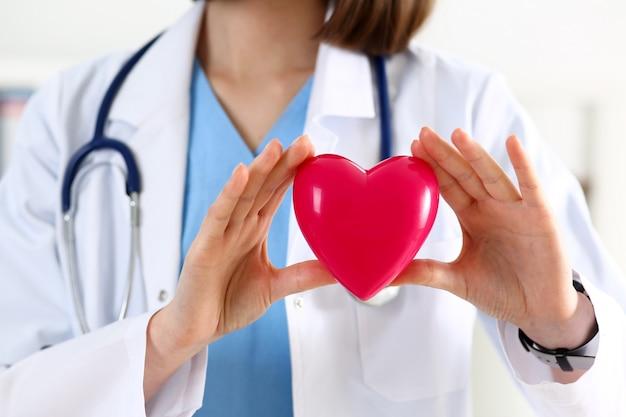 Vrouwelijke geneeskunde artsenhanden die rood hart houden