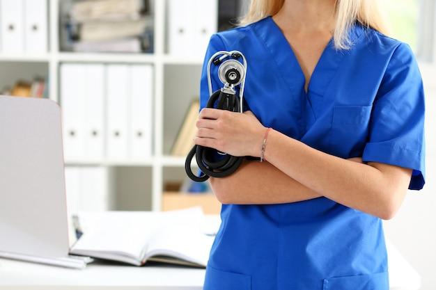Vrouwelijke geneeskunde therapeutist arts handen gekruist op haar borst