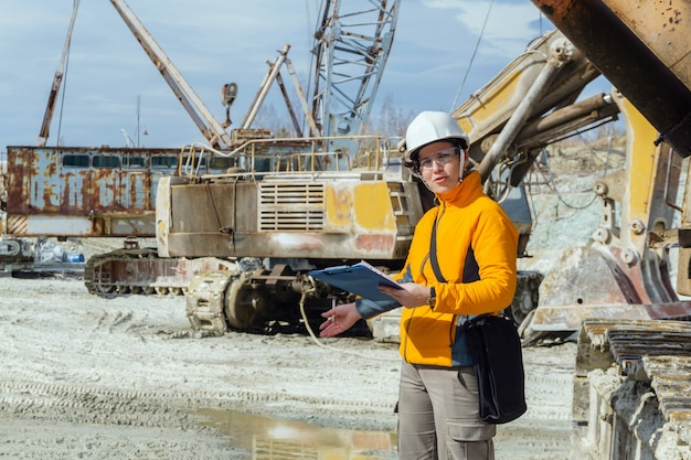 Vrouwelijke geoloog of een mijningenieur schrijft iets in een kaartdoos te midden van een steengroeve met bouwmachines