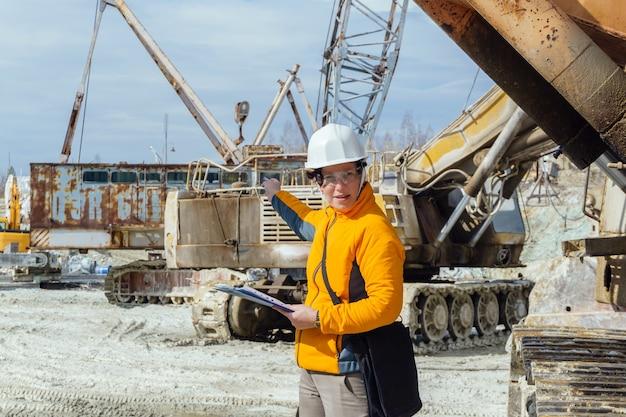 Vrouwelijke geoloog of een mijningenieur te midden van een steengroeve met bouwmachines die iets bespreken, gebaren