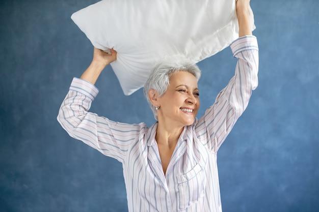 Vrouwelijke gepensioneerde die een zijdeachtige pyjama draagt, lacht, in een goed humeur is terwijl hij plezier maakt in de slaapkamer, armen opheft, veren kussen boven haar hoofd houdt