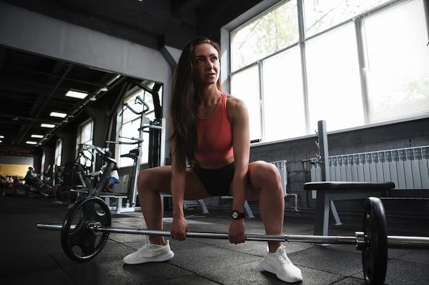 Vrouwelijke gewichtheffer trainen met barbell in sportstudio