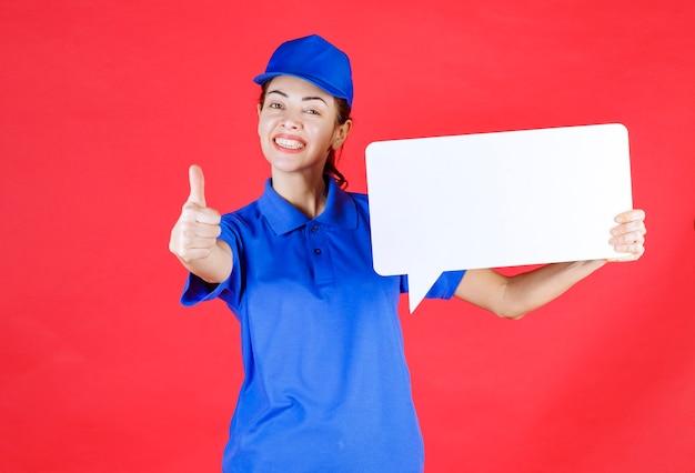 Vrouwelijke gids in blauw uniform met een wit rechthoekig infobord en een teken van plezier.