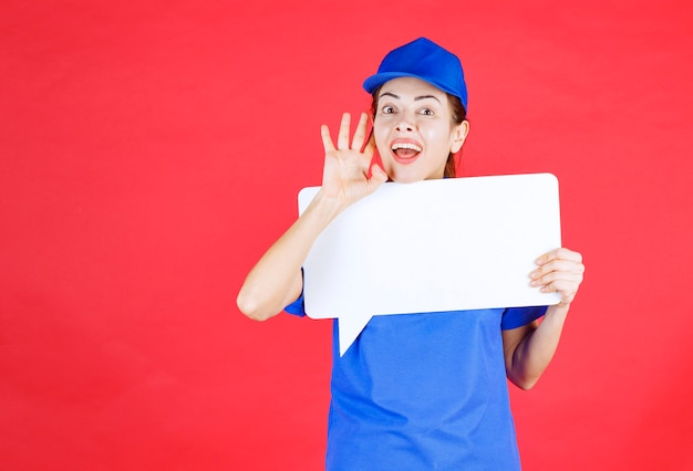 Vrouwelijke gids in blauw uniform met een wit rechthoekig infobord en oren openend en schreeuwend.