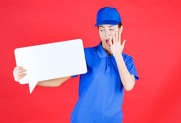 Vrouwelijke gids in blauw uniform met een wit rechthoekig infobord en ziet er doodsbang en verrast uit.