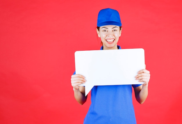 Vrouwelijke gids in blauw uniform met een wit rechthoekig infobord.
