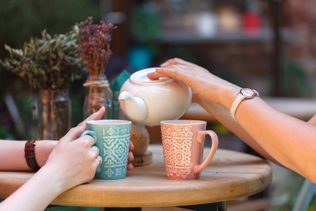 Vrouwelijke gietende thee in ochtendkoffie