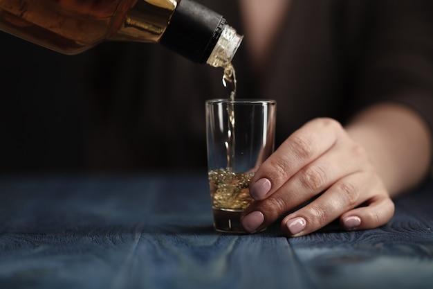 Vrouwelijke gietende whisky aan glasschot
