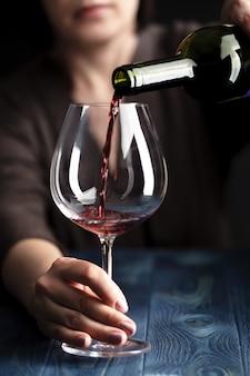 Vrouwelijke gietende wijn binnen aan wijnglas