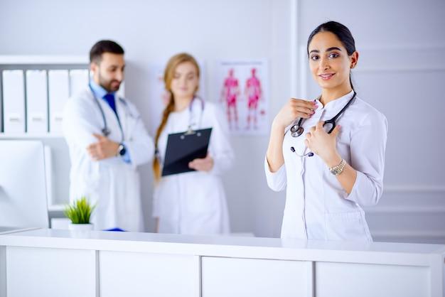 Vrouwelijke glimlachende arabische arts met stethoscoop die zich voor haar team in het ziekenhuis bevindt