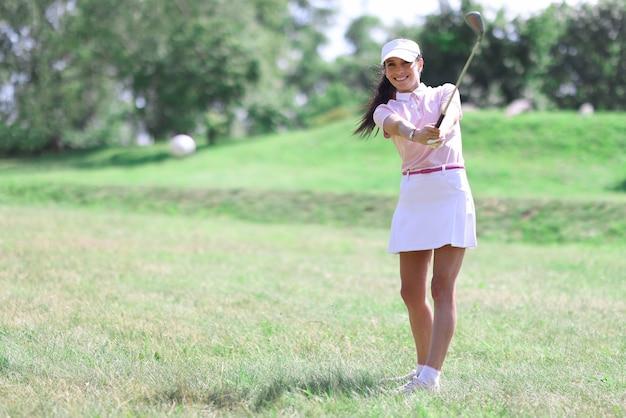 Vrouwelijke golfer raakt bal met clubclose-up