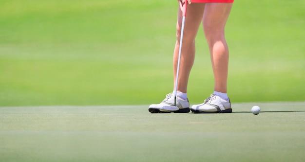 Vrouwelijke golfspeler die op groen zet.