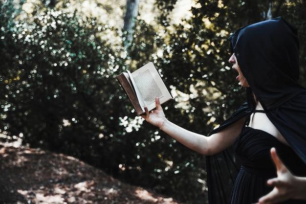 Vrouwelijke goochelaar lezen spreuk in het kreupelhout