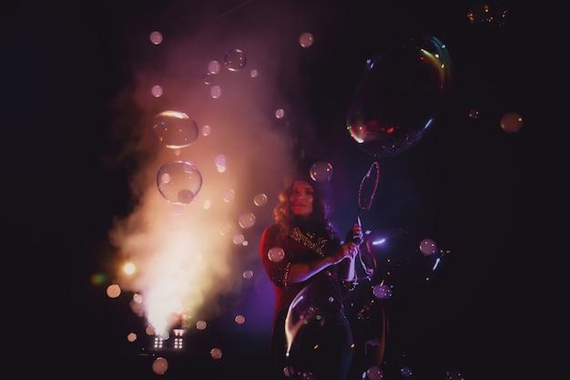 Vrouwelijke goochelaar maakt show met zeepbellen, een illusionist in theatrale kleding, op zwarte achtergrond