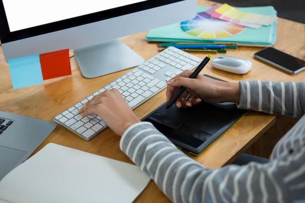 Vrouwelijke grafisch ontwerper die bij bureau werkt