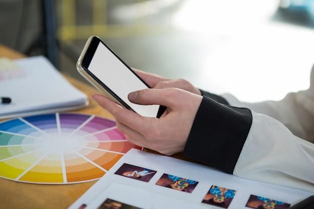 Vrouwelijke grafisch ontwerper die mobiele telefoon met behulp van bij bureau